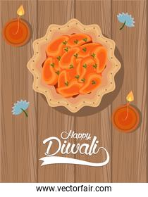 happy diwali celebration with two candles and food in wooden background