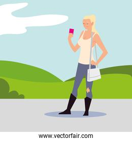 blonde woman using smartphone in the street