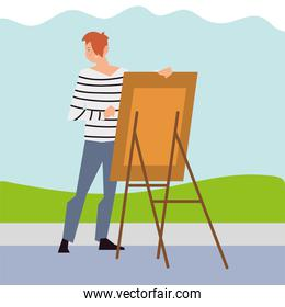 young man painting with canvas in the park
