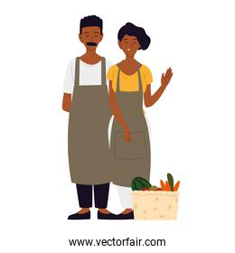 couple wearing apron with basket filled fruit and vegetable