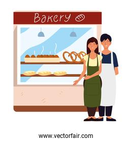 couple with apron in front of their bakery
