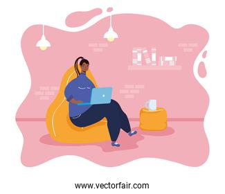 afro ethnic woman using laptop in livingroom