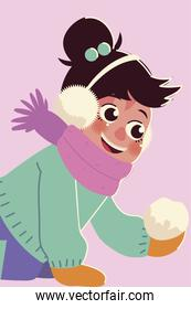 smiling little girl with winter earmuffs and snowball