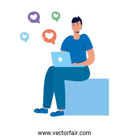 young man seated using laptop and social media icons