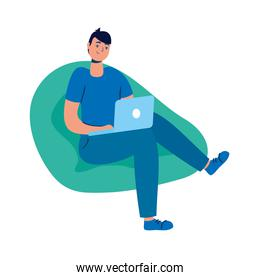 young man seated in sofa using laptop technology