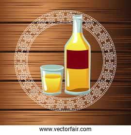 mexican tequila bottle and cup in wooden background