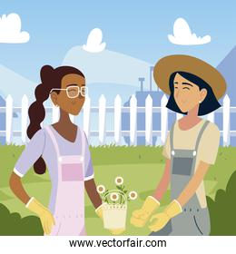 gardening, smiling women with flowers in the yard