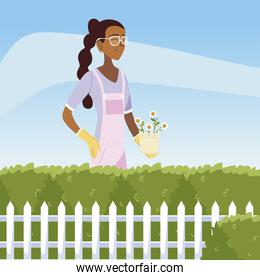 gardening, woman with flowers in pot bushes and fence garden