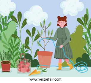 gardening, girl spraying water to a plant with hose,