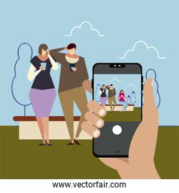 hand with smartphone taking a photo people using smartphones in the park