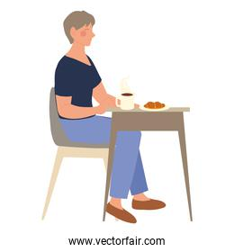 woman sitting at the table in cafe with cup and croissant