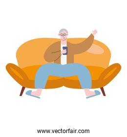 grandfather using smartphone technology seated in sofa