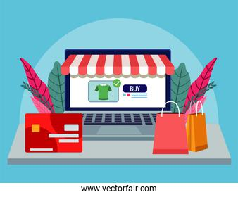 online shopping technology in laptop with credit card and bags