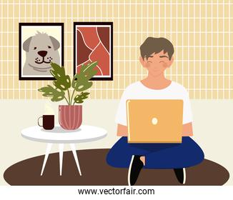 young man using laptop working sitting on the room floor, work at home