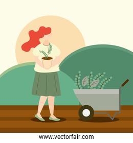 woman carrying potted plant and wheelbarrow with gardening