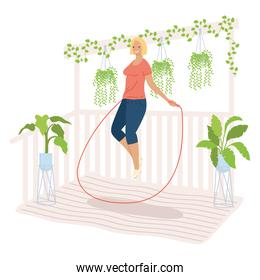 athletic woman jumping rope in the garden