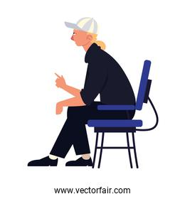 young man wearing cap sitting on chair isolated