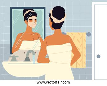 beautiful woman moisturizing face with cream or cleansing lotion in front of mirror, skincare